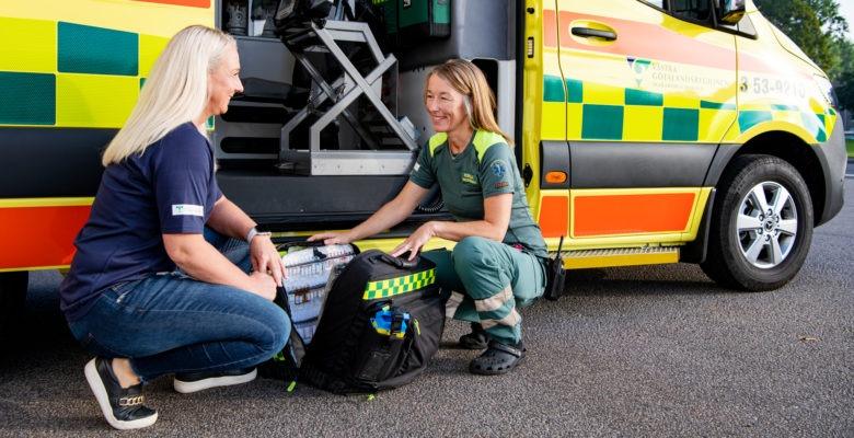 Två kvinnor sitter på huk och pratar framför en ambulans