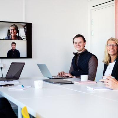 En grupp personer i ett rum har videomöte med en annan grupp personer