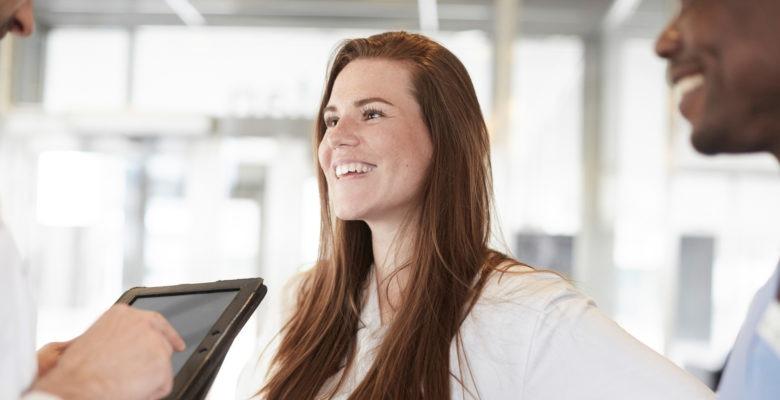 Kvinna som arbetar i vården ler mot en kollega.