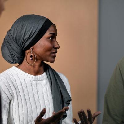 Kollegor av olika etnicitet pratar med varandra på ett möte