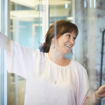 leende kvinna i kontorslandskap som pekar på lappar uppsatta på en vägg. Intill henne en lampa.