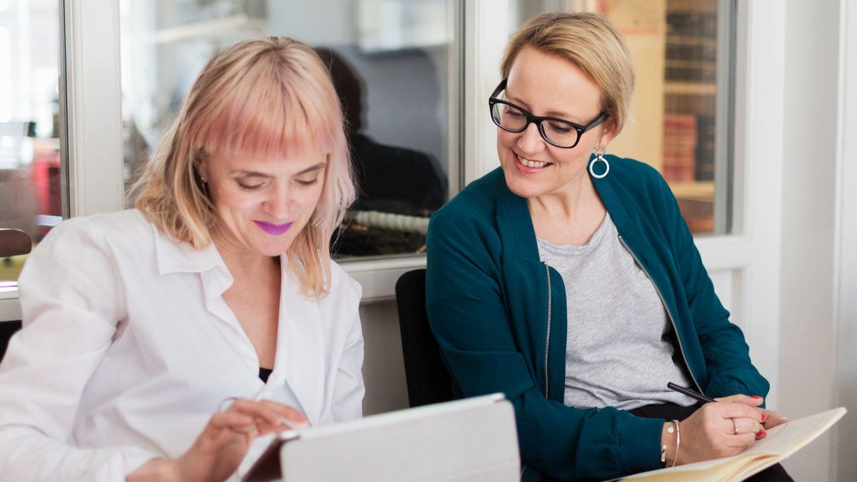 två kvinnor sitter brevid varandra mdd en liten dator respektive anteckningsblock. Kvinna med blocket tittar leende på något på skärmen på datorn.
