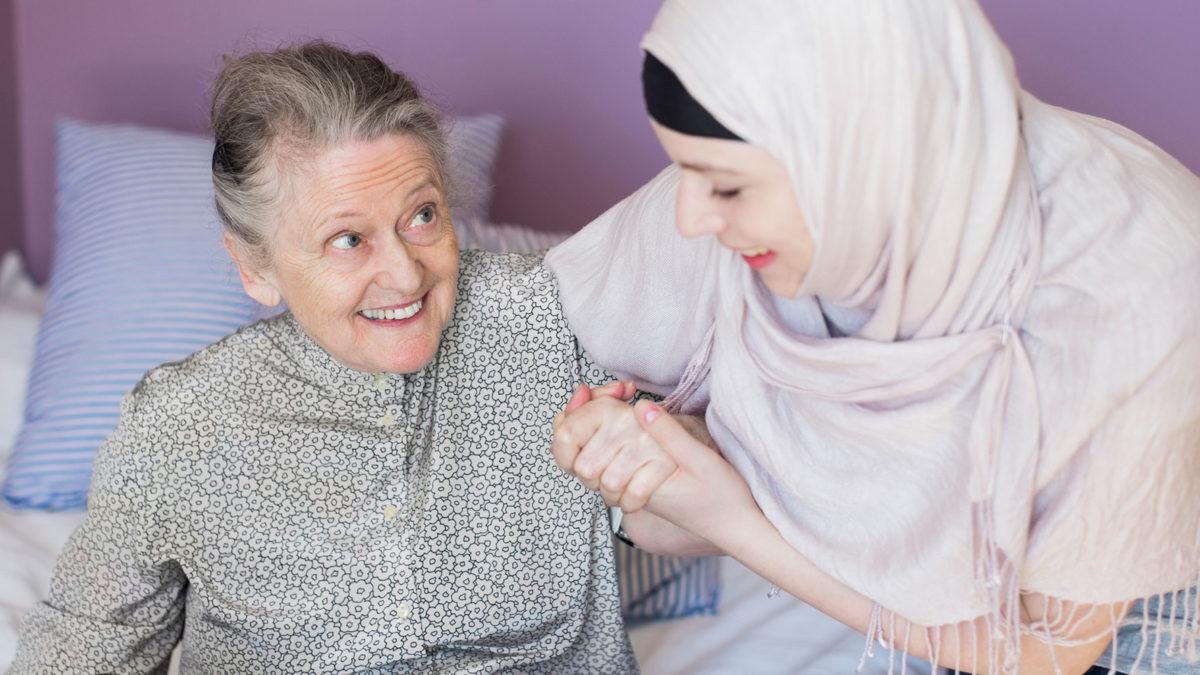 gammal dam får hjälp upp från sängen av leende kvinna i sjal.