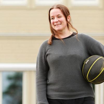 kvinna med fotboll på skolgård