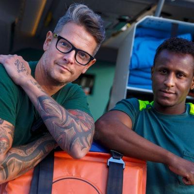 två män från räddningstjänsten utanför en ambulans. Tittar in i kameran.